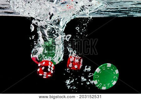 Red Dice And Chips In The Water On Black Background