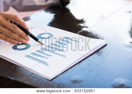 Businesswoman With Financial Summary Graph Sitting Outside Office Building. Young Asian Woman Analyz