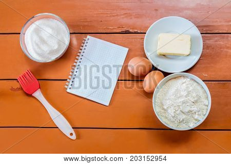 Eggs butter flour sugar and notebook on painted rustic wooden background.