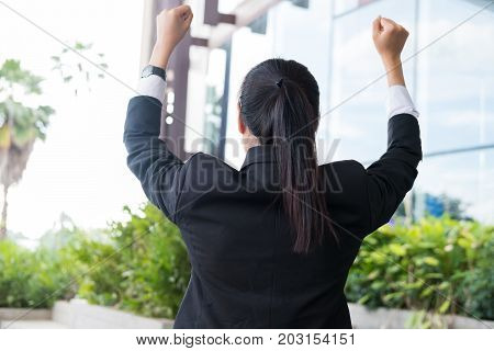 Young Businesswoman Feeling Successful Outside Office Building. Asian Woman Raising Her Hands With H