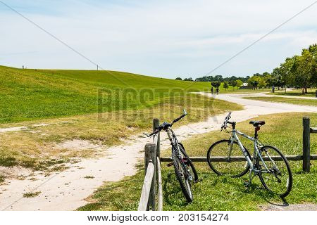 VIRGINIA BEACH, VIRGINIA - JULY 10, 2017:  Two bicycles rest on a fence while people trail hike at Mount Trashmore Park, a city park created on the site of a former landfill in 1974.