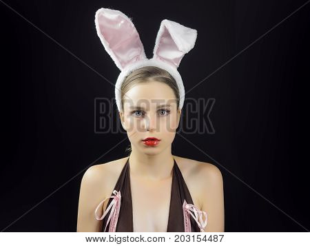 Woman with red lips wearing rabbit ears. Playboy girl posing on black background.  Easter holiday concept.