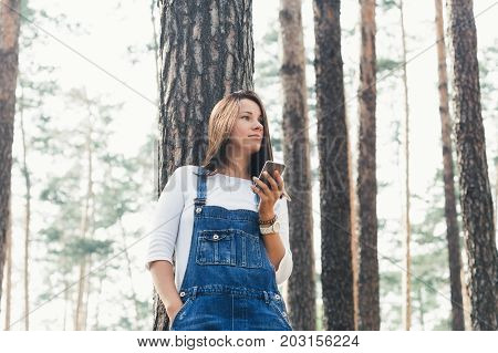 Beautiful young woman in jeans overalls with smartphone standing in woodland in the evening