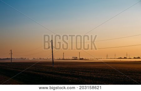 Morning haze in field and electric poles with wires at dawn, toned
