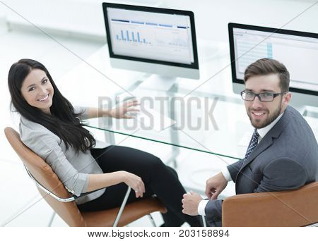 Senior manager and assistant sitting at the desk.