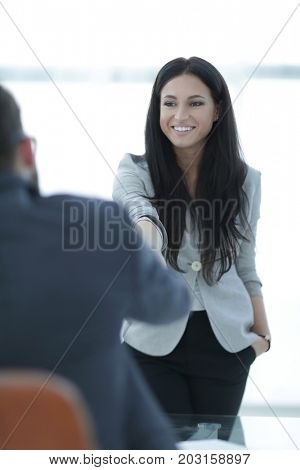 business woman welcomes colleague with handshake