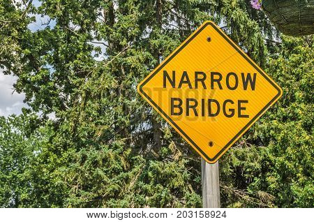 Yellow and black sign lets drivers know there is a narrow bridge ahead