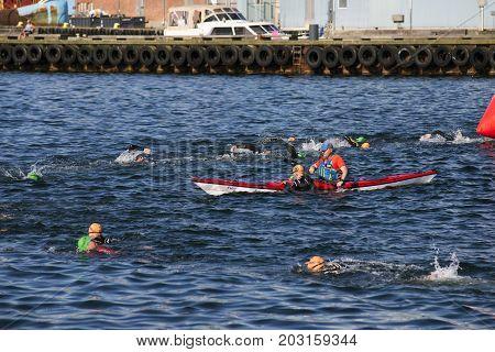 Fredericia Denmark - September 3 2017: Triathletes swimming the triathlon competition Challenge Denmark in Fredericia Harbor. Tired swimmer holding onto kayak.