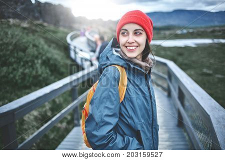 young woman hiker walking in beautiful mountains in Thingvellir valley, Iceland