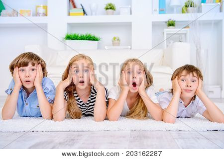 Four funny children lie on the floor at home with very surprised faces. Child concept.