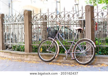 Vintage rustic retro bicycle close to iron fence. Colored horizontal outdoors image.