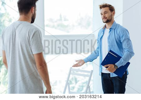 Sit down please. Nice pleasant handsome therapist holding a folder with documents and looking at his patient while inviting him to sit down