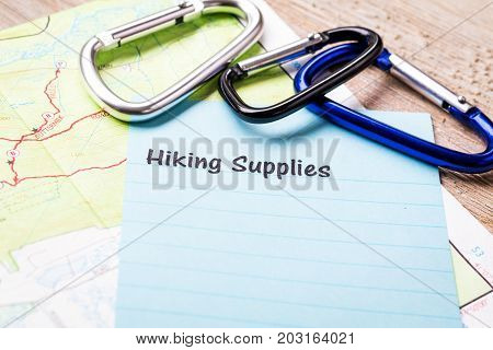 Hiking Supplies list concept on notebook and wooden board with map and carabiners