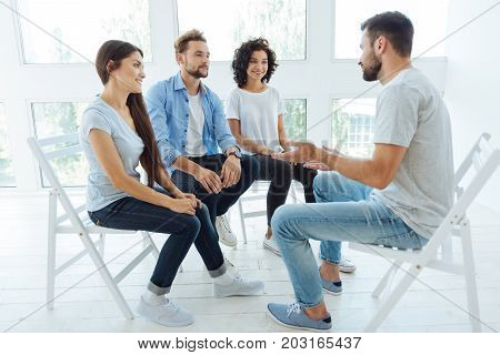 Teambuilding coach. Handsome positive nice man sitting in front of his group and talking to them while working as a teambuilding coach