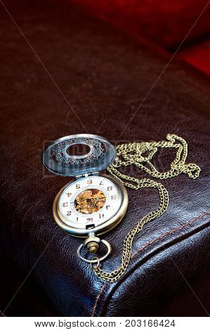 Metal elegant antique pocket timepiece on leather background. Indoors close-up.