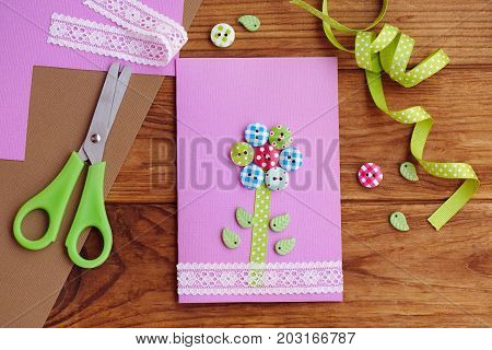 Greeting card with a flower made of wooden buttons, decorated with lace. Beautiful paper card crafts for mom's birthday or mother's day. Tools and materials on a table. Children's workplace. Top view