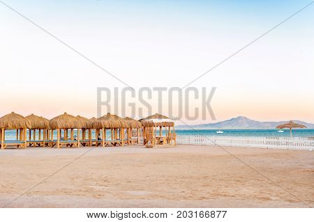 Wooden beach houses with straw roof on the egyptian seaside. Summer sunrise outdoors.