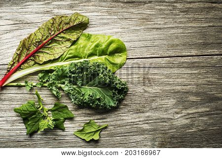 Vegetable healthy green leaves. Kale swiss chard and spinach on wooden background