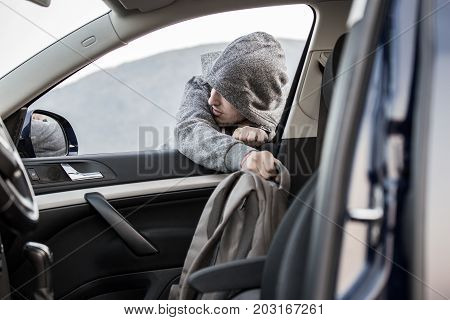 A Thief, A Criminal, Thrust His Hand Out Of The Car Window And Takes A Backpack, Steals Private Prop