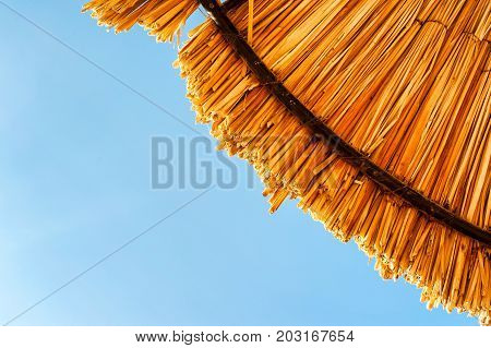 Wattled straw beach umbrella on clear blue sky background. Outdoors summertime multi colored closeup horizontal image. View from below.