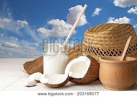 Cowboy Hat, Half Of Coconut, Pieces Of Coconut, Coconut Flakes, Glass Jar With Coconut Milk On Blue