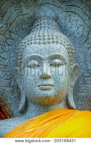 Granite Buddha image dressed with yellow robes in Buddhist temple