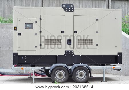 Big Backup Mobile Generator for Office Building Connected to the Control Panel with Cable Wire to the Office Building