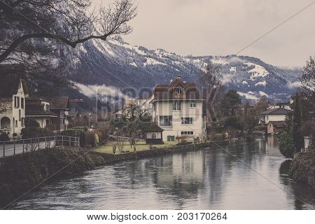Vintage village with evergreen tree in front of beautiful sierra covered in fog mist and snow, The riverside house has three storey behind canal reflect it with mountain range Background, Curve canal flow along small town in Interlaken at Switzerland