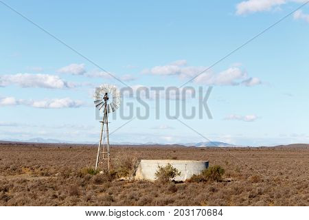 Windmill With A Dam In The Dry Field Of The Central Karoo