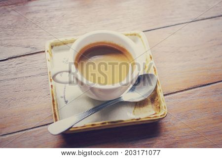 Cup of  hot Espresso Coffee with crema on wooden background with copy space ,Vintage sepia tone.