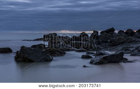 Cornish coast at night with rocks and clouds in the sky beach at Saint Ives Cornwall England.