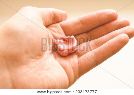 pink chewing gum and man hand isolated on white background close up