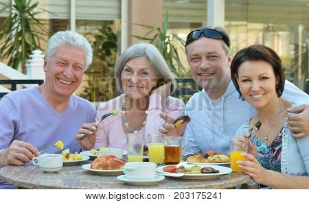 Portrait of a family having breakfast together outdoors