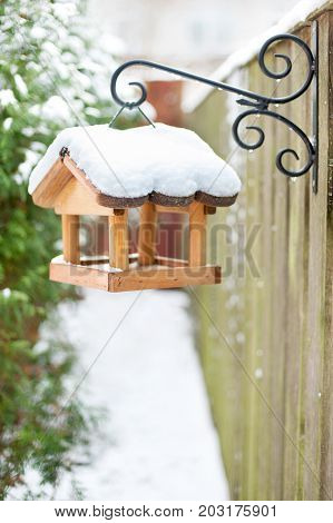 Hanging wooden bird feeder covered by snow in winter. Outdoors vertical closeup image.