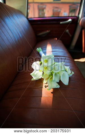 Callas flowers festive bouquet in sunbeam on rear leather seats in vintage car. Vibrant colored vertical image indoors image.