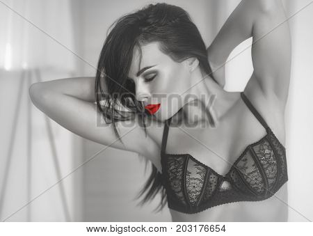 Sexy brunette woman in bra posing with closed eyes sensuality passions and desire. Selective coloring black and white with red lips