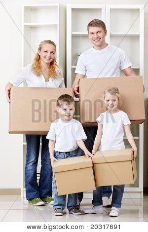eine Familie mit zwei Kindern tragen Kasten