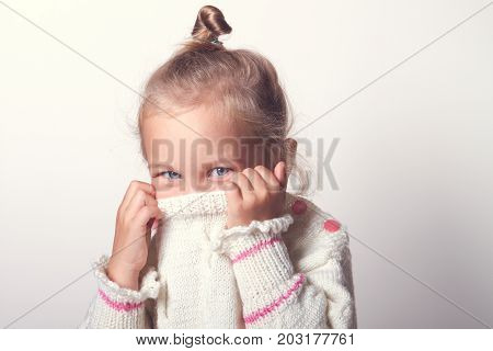 Portrait of a charming little girl in beige sweate. hides his nose. child playing peekaboo.  hiding inside the neck of her pullover while smiling at the camera. toned