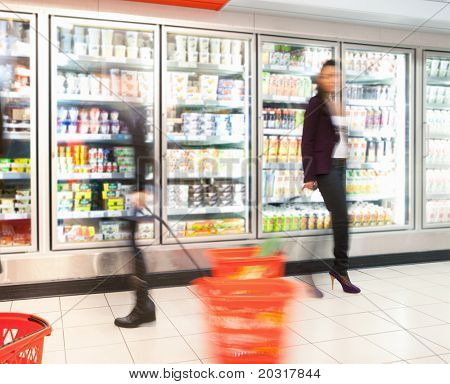 Blurred motion of people walking near refrigerator in shopping centre with baskets
