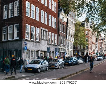 Amsterdam Netherlands - 25 April 2017: Tourists walk along the street. Adult man rides a bicycle in historical part of Amsterdam. The houses tilted in different directions.