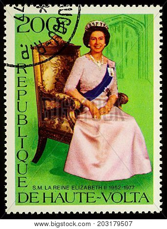 Moscow Russia - September 06 2017: A stamp printed in Upper Volta (Burkina Faso) shows Queen Elizabeth II sitting in a chair circa 1977