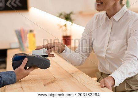 partial view of smiling woman making payment with credit card in cafe