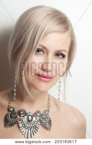 Portrait Of Beautiful Young Blonde Woman In Ear-rings And Necklace