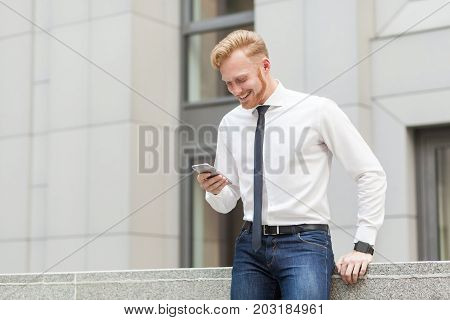 Redhead And Bearded Business Man Have A Video Conference In Hes Smart Phone. Business Concept.