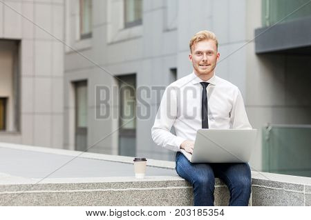 Young Adult Businessman Working Outsourcing, Looking At Camera And Toothy Smile.
