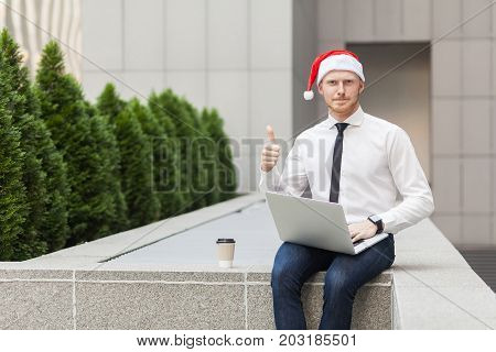 Red Head Man In Santa Hat, Working Outdoor, Thumbs Up And Looking At Camera.