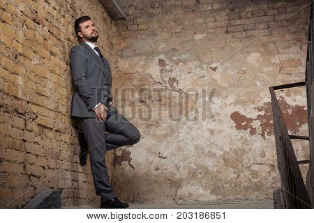 serious imposanteman in a gray suit standing in an urban environment. Studio shoot