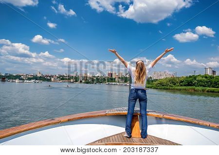 Back view beautiful happy female traveller on yacht