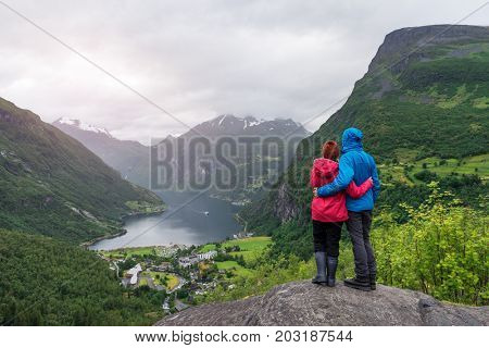 A young married couple is standing on a rock with looking at the fjord and mountains. Tourist village of Geiranger and the Geirangerfjord, Norway
