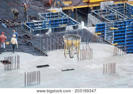 Construction of concrete foundation of new building. Aerial view of construction site workers leveling cement in building site